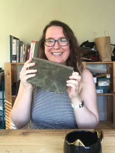 Smiling woman holds zippered pouch behind wood table. A bookshelf with books are in the background. A mug sits on the table in front of her.