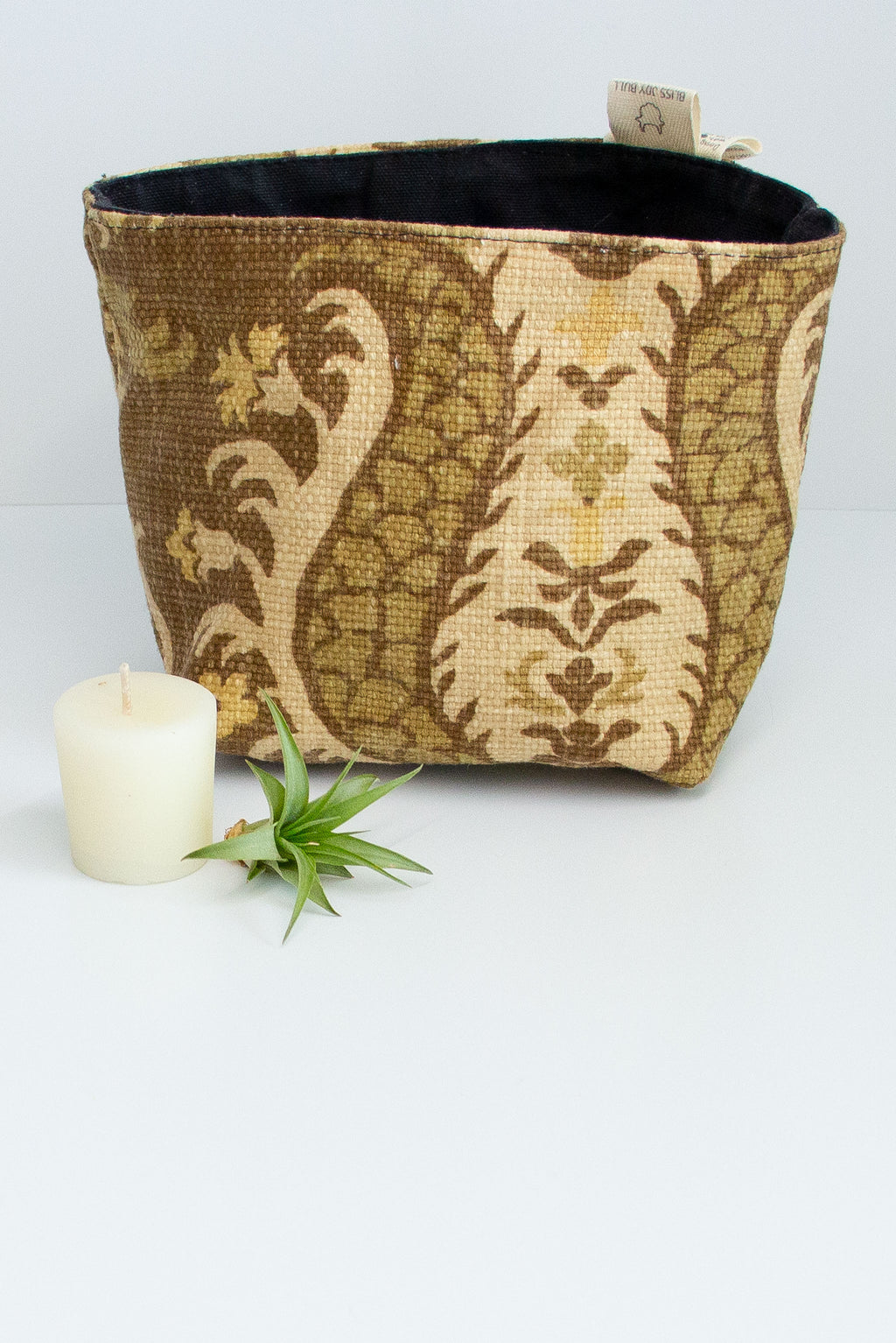 A fabric basket in light yellow and dark olive fleur de lis pattern with a black lining. A small votive candle and air plant sit next to it on a white background.