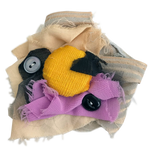 Load image into Gallery viewer, flower-like hair pin made from yellow fabric covered bottle cap, black buttons, silk peach colored scraps, and lavender and black fabric scraps.