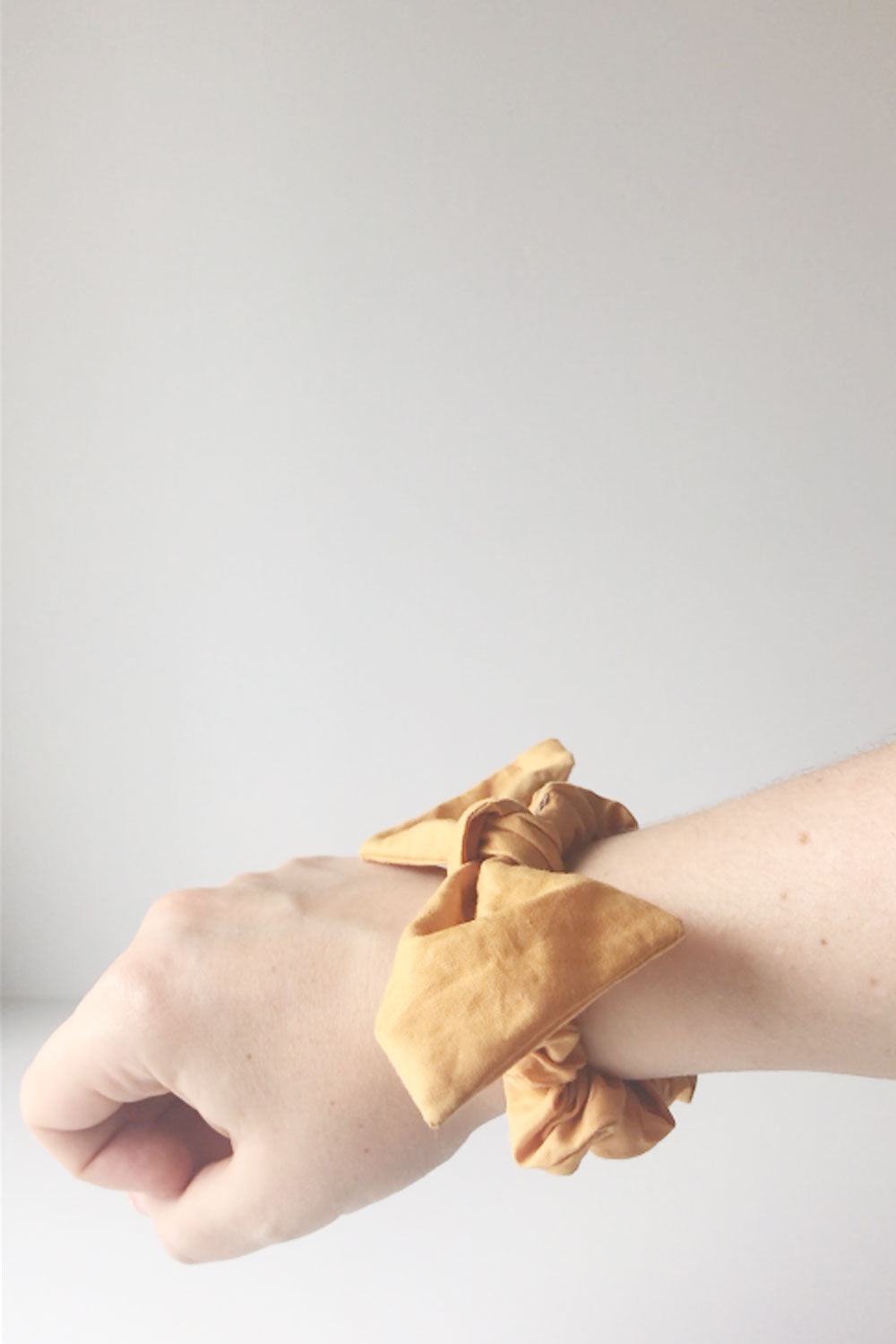 fabric orange hair bow scrunchie worn on a wrist