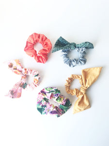 A circle of 5 classic and bow hair scrunchies sit on a white background.