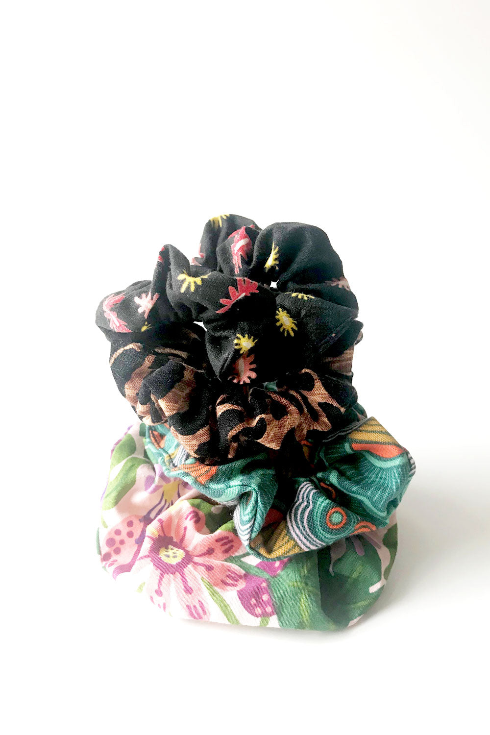 a stack of hair bow and regular hair scrunchies in various colors and prints