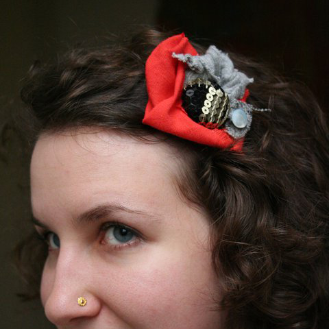 Profile of a woman with a red, grey and sparkly flower-like fabric scrap hair pin in her hair.