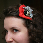 Load image into Gallery viewer, Profile of a woman with a red, grey and sparkly flower-like fabric scrap hair pin in her hair.