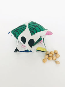 Two square hand warmers sit on a white background with a small hand full of dried cherry pits. The hand warmers have a tropical print fabric in large green leaves, yellow, pink, and navy blue flowers. Abstract shapes in black. All on a white background.