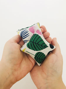 Two square hand warmers are held in two overlapping hands. The hand warmers have a tropical print fabric in large green leaves, yellow, pink, and navy blue flowers. Abstract shapes in black. All on a white background.