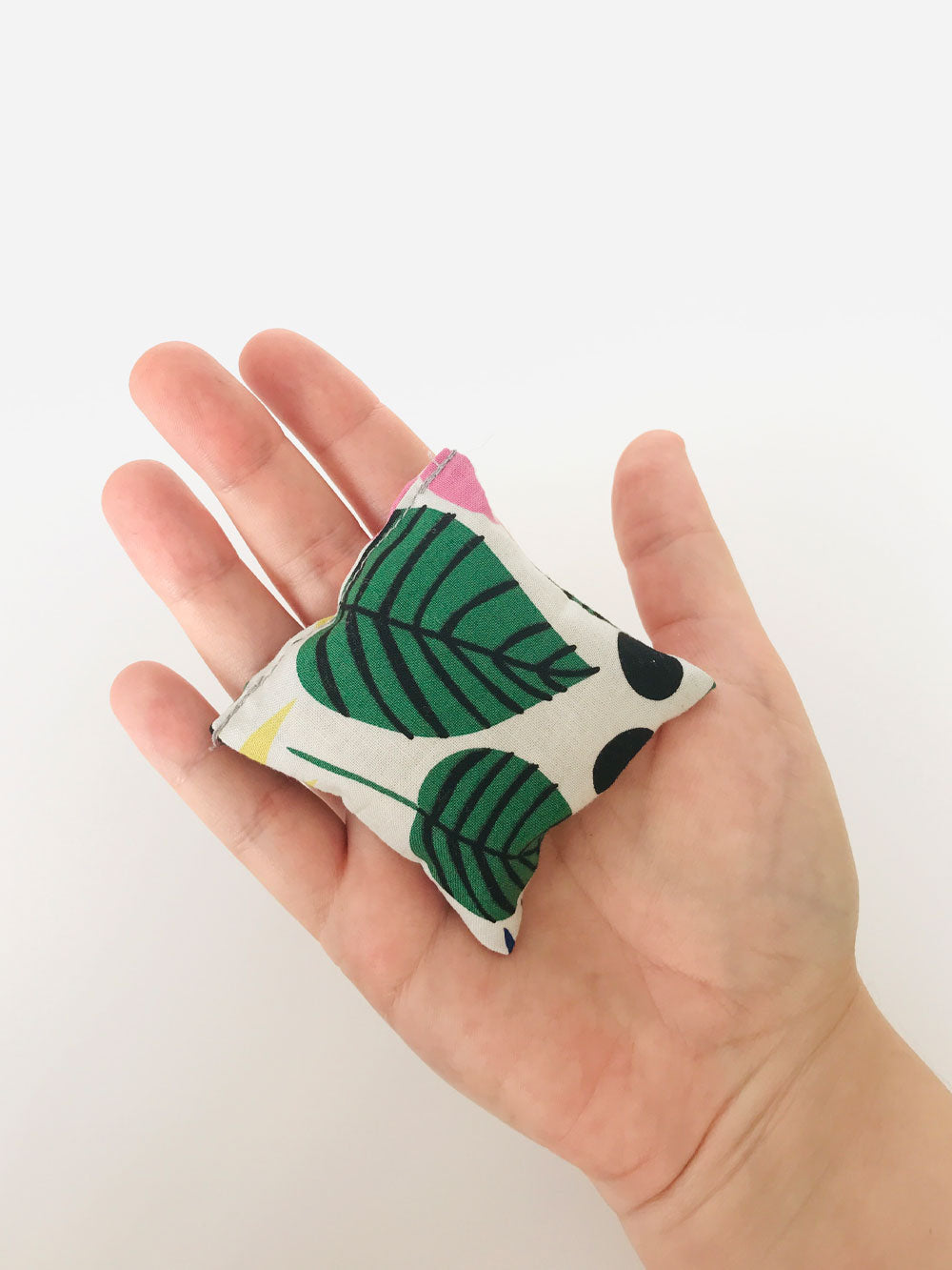 A single square hand warmer is held in an open hand. The hand warmer has a tropical print fabric in large green leaves, yellow, pink, and navy blue flowers. Abstract shapes in black. All on a white background.