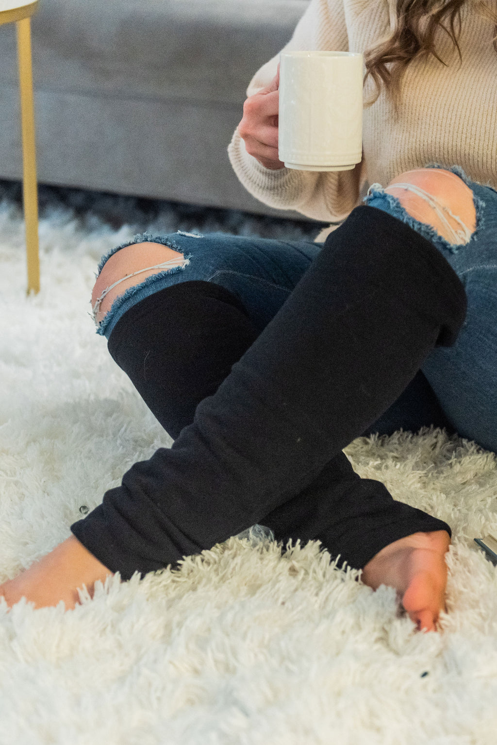 woman sits on a white plush fuzzy carpet while holding a white mug of tea. She is wearing a beige knit sweater, jeans, and black leg warmers that cover her legs below the knee.