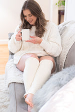 Load image into Gallery viewer, woman sits on a grey couch with a white knit blanket and grey fuzzy pillow. She is wearing a chunky cream knit sweater and cream leg warmers below her knees. She is smiling while looking down and holding a white mug with tea.