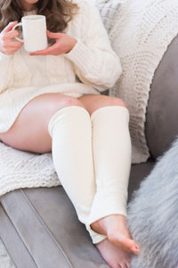 woman in cream chunky knit sweater sits on grey couch with cream knit blanket, holding a white mug of tea and wearing cream leg warmers below the knee