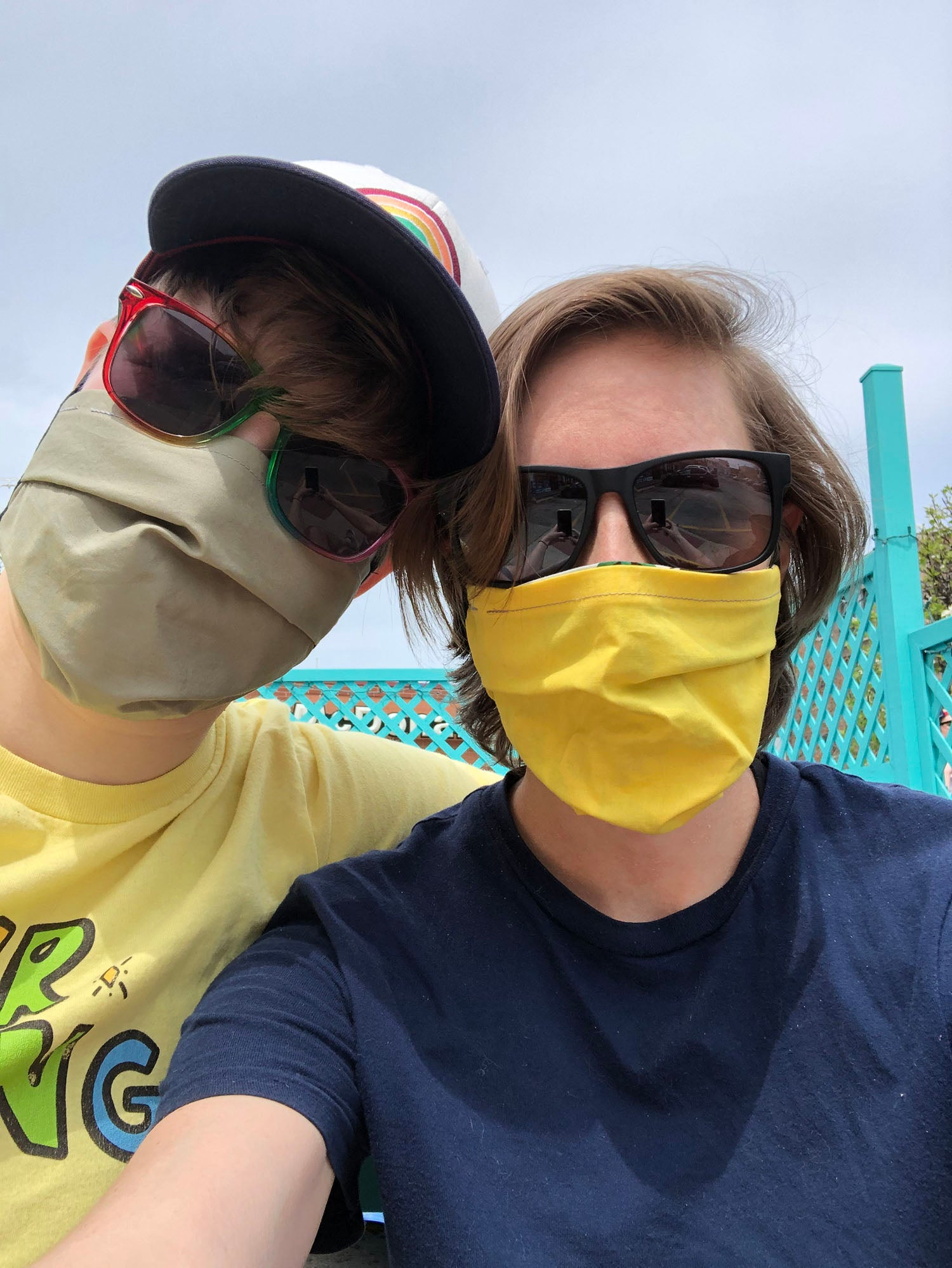 A couple sitting outside rest their heads together. One person wears a hat with a rainbow, rainbow sunglasses and a laurel green face covering; the other person wears black sunglasses and a yellow face covering