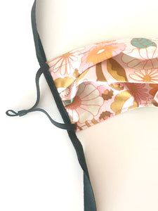 Close up of vintage-like floral print fabric face mask with black adjustable elastic ear loops and cotton ties. Fabric features large white and pink flowers outlined in orange with green and tan leaves.