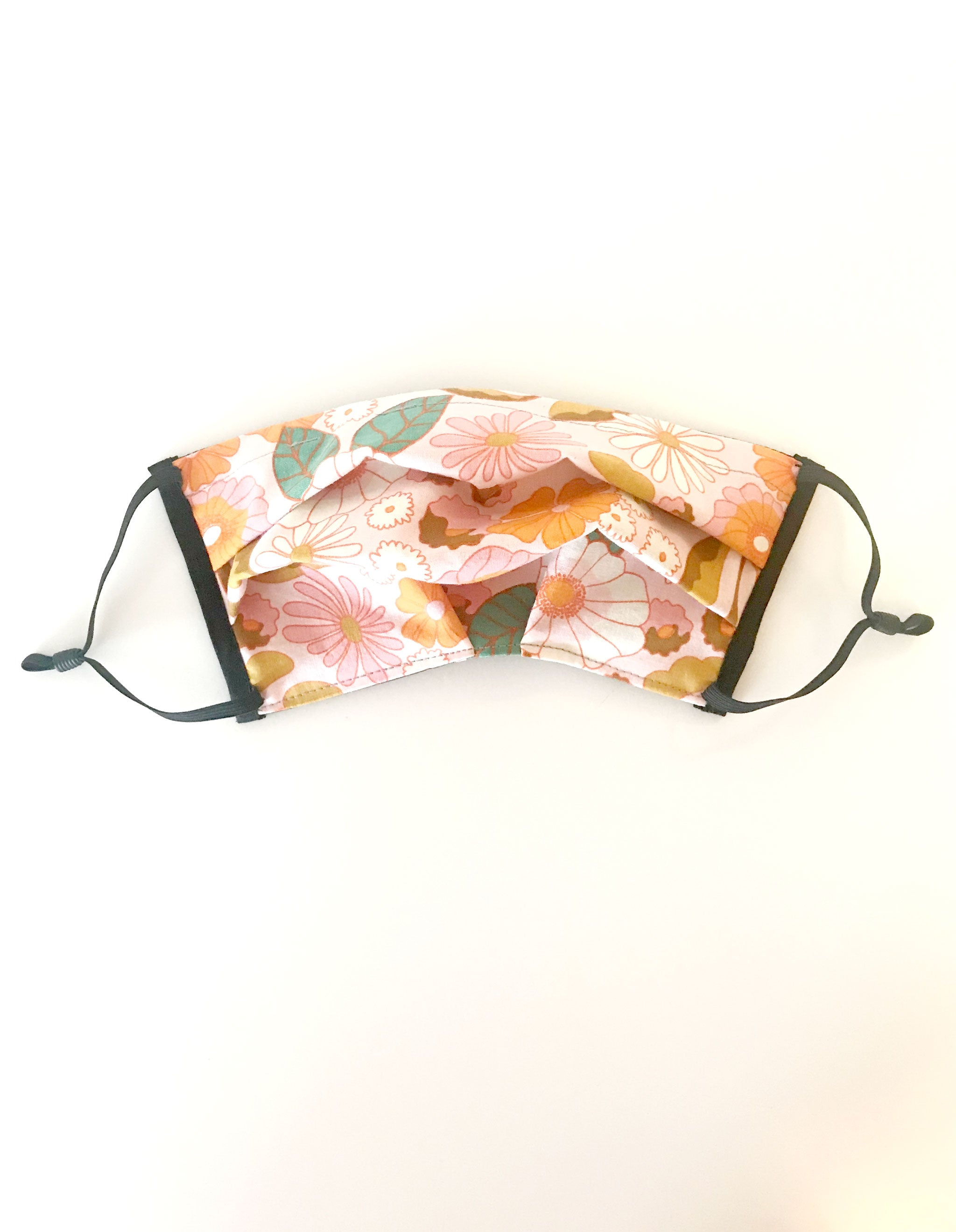 vintage-like floral print fabric face mask with black adjustable elastic ear loops. Fabric features large white and pink flowers outlined in orange with green and tan leaves.