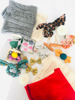Load image into Gallery viewer, An assortment of leg warmers, hair scrunchies, bow earrings, wood earrings, fabric square hand warmers, and small votive beeswax candles arranged on a white background.