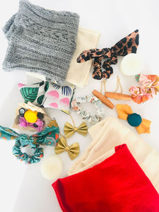 An assortment of leg warmers, hair scrunchies, bow earrings, wood earrings, fabric square hand warmers, and small votive beeswax candles arranged on a white background.