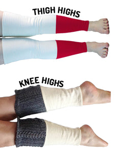 Two pairs of horizontal legs wearing leg warmers on a white background. On the top thigh high leg warmers are 2/3 red on the bottom with white fleece tops. Text curves along the shape of the top leg reads THIGH HIGHS. On the bottom knee high leg warmers are 2/3 white fleece on the bottom with grey knit tops. Text curves along the top leg reads: KNEE HIGHS.
