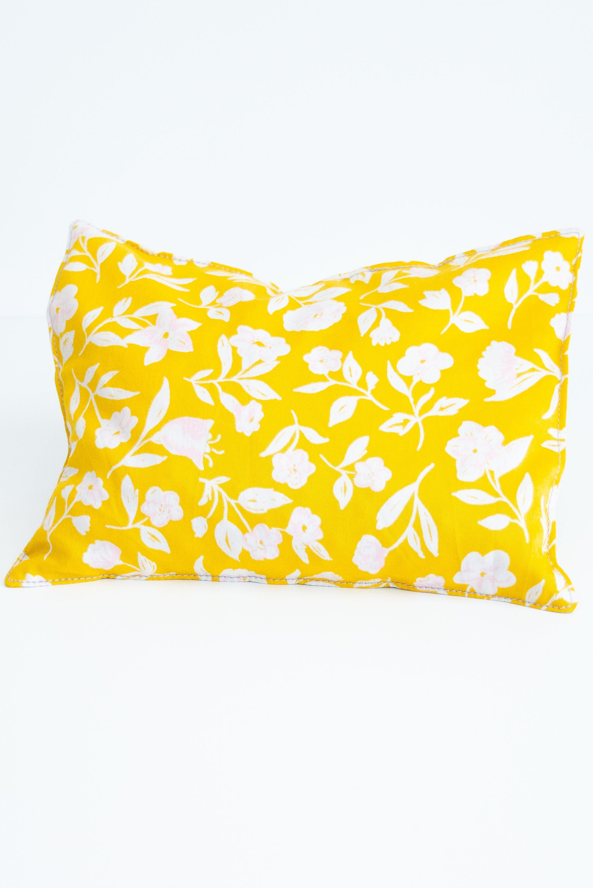 Rectangle cherry pit grain bag with white and print floral on yellow background  sits on white background.