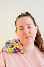 Load image into Gallery viewer, Woman with eyes closed and tilted head has a cherry pit grain bag draped across her right shoulder.
