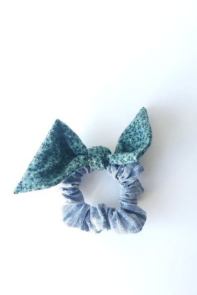 mystery hair bow scrunchie - this bow features a teal fabric with small black and white flowers for the bow of the hair scrunchie; the main part of the scrunchie is blue and white ticking fabric