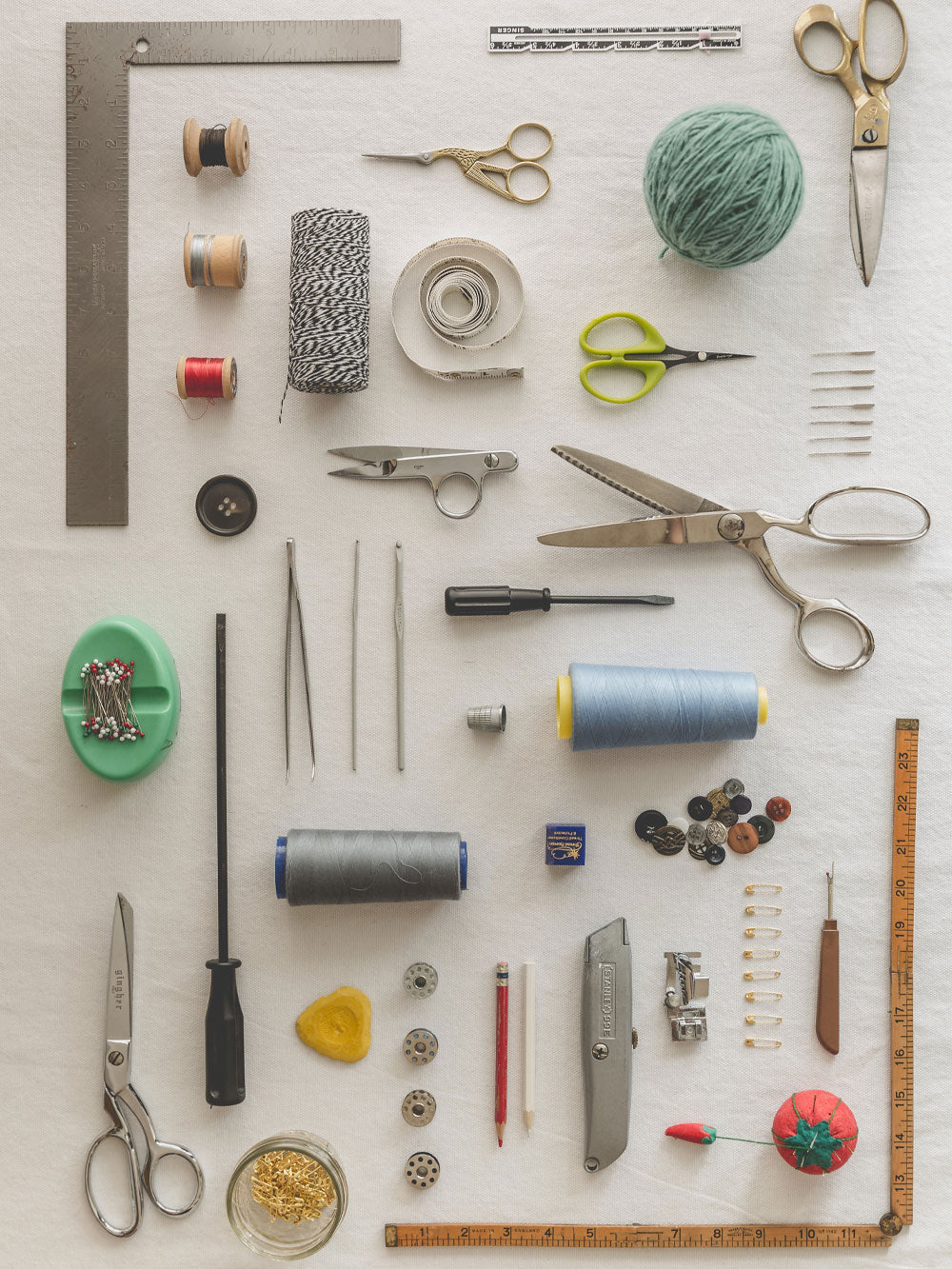 All of the supplies needed for any sewing project set up in perfect order on white linen. Needles, pins, thread, scissors and measuring tools,