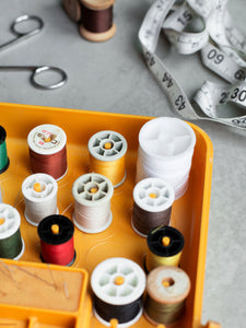 Spools of sewing thread in a yellow tray and accessories are placed on a grey table.