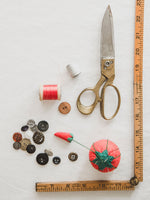 Load image into Gallery viewer, scissors, buttons, thread, tomato pin cushion and ruler on white background