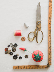 scissors, buttons, thread, tomato pin cushion and ruler on white background