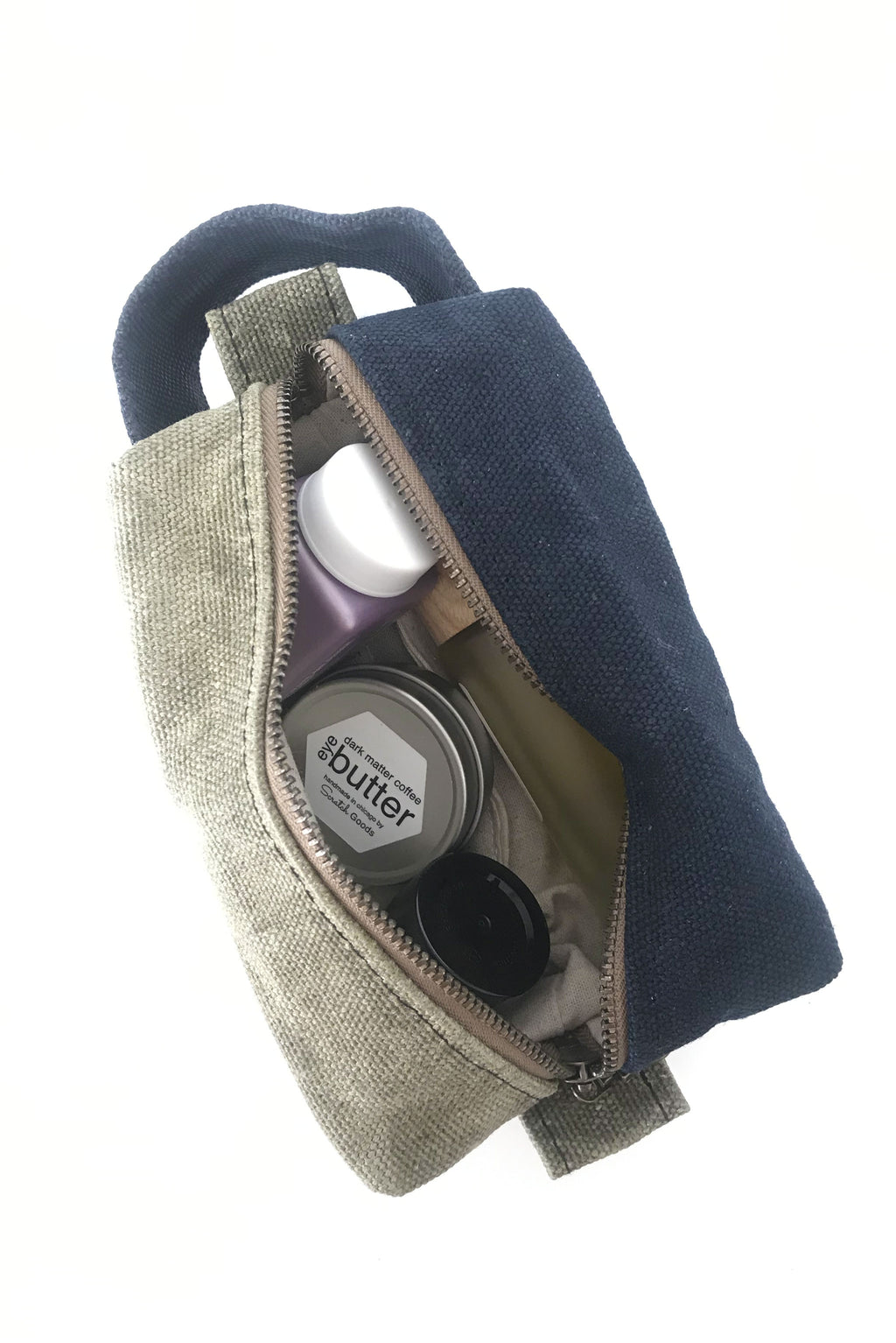 small waxed canvas toiletry bag with handle and brass zipper. The bag is open and contains small toiletries inside. The bag is half sage green and half dark navy blue.