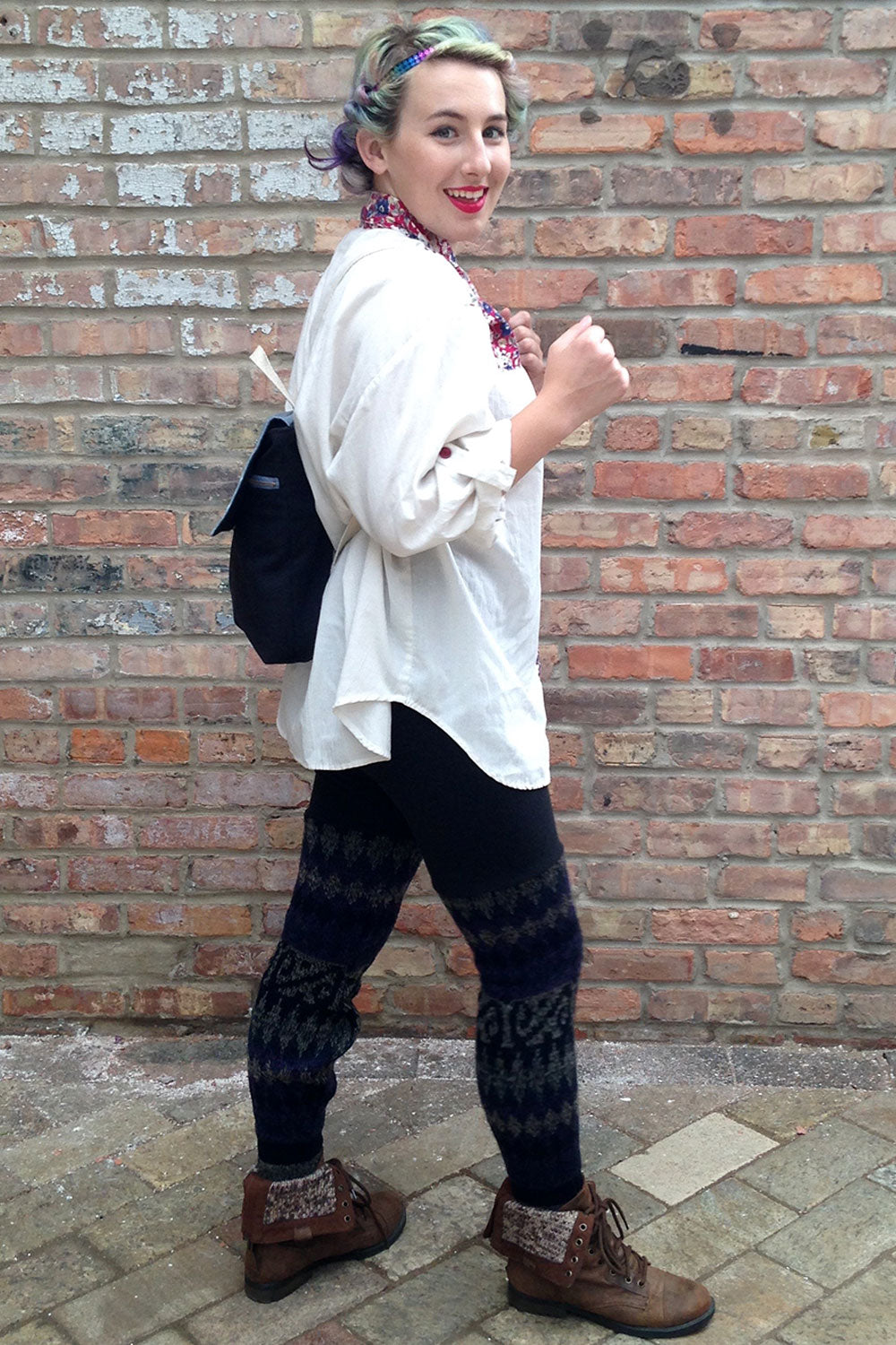 woman wear oversized button down, mini backpack, and sweater leggings