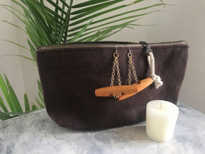 dark brown zipper pouch with wood toggle buttons on gold chain earrings with beeswax votive candle on marble surface with fern plan in the background
