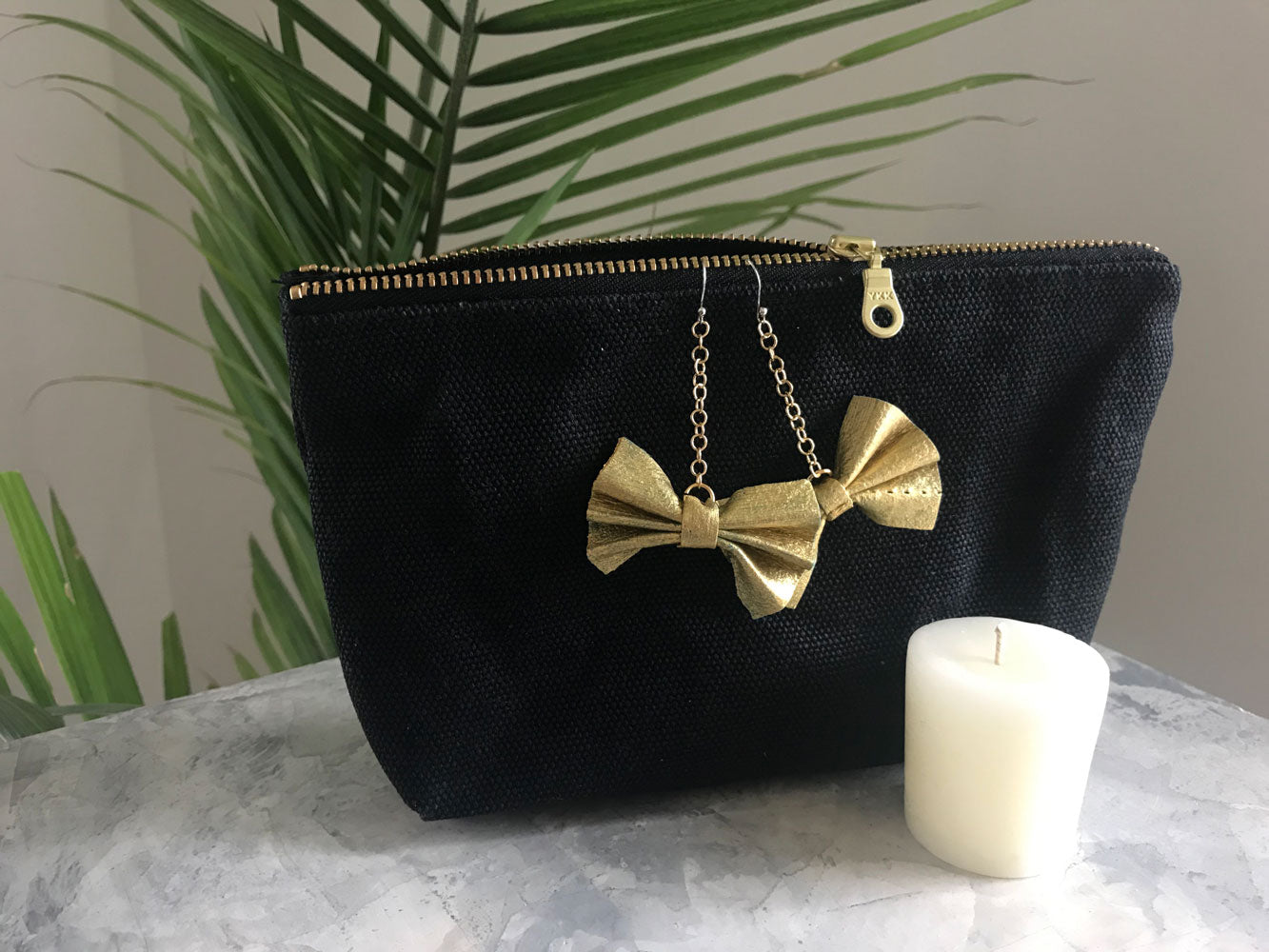 black zipper pouch with gold painted leather bow on gold chain earrings with beeswax votive candle on marble surface with fern plan in the background
