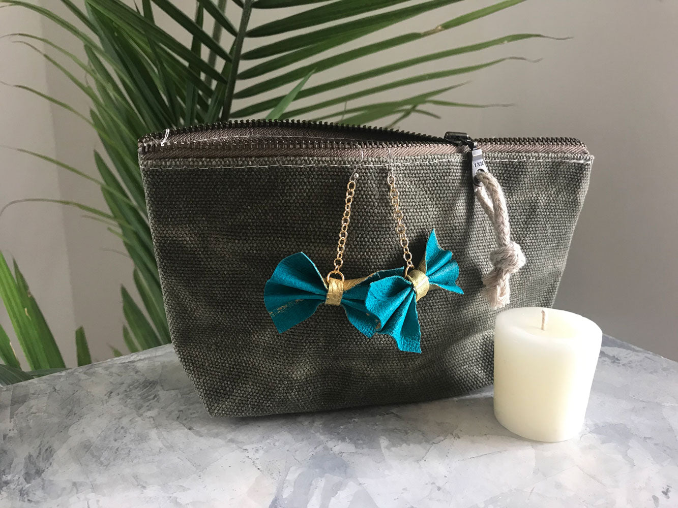 sage green zipper pouch with green leather bow on gold chain earrings with beeswax votive candle on marble surface with fern plan in the background