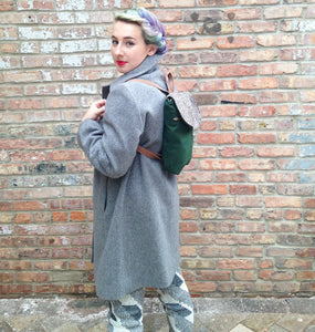 woman is mostly turn away from the camera, with rainbow hair tied up, she is wearing bright red lipstick, wearing a grey wool coat the hits right above the knee and grey and white patterned leggings. She wears a green small backpack on her back with a tweed flap and pink tweed straps