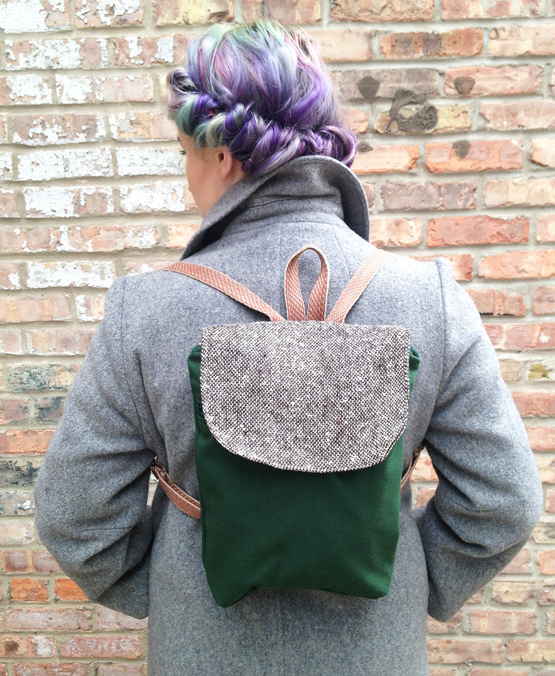 woman has her back towards camera, with rainbow hair tied up wears a grey wool coat. She wears a green small backpack with tweed flap and pink tweed straps