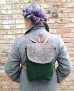 Load image into Gallery viewer, woman has her back towards camera, with rainbow hair tied up wears a grey wool coat. She wears a green small backpack with tweed flap and pink tweed straps