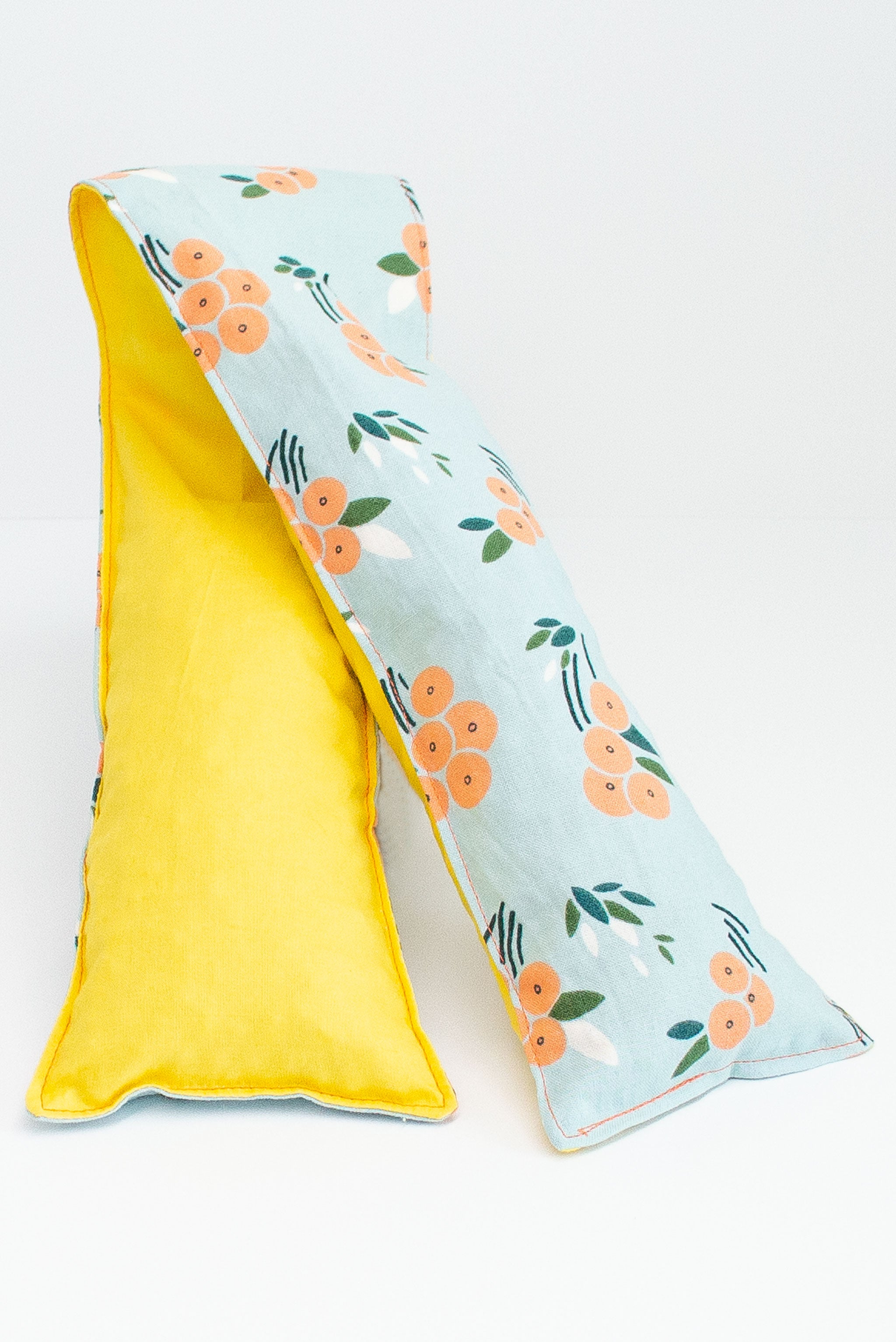 Long and skinny cherry pit grain bag on white background. Half yellow, half peach floral print on blue background.