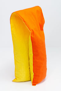Long and skinny cherry pit grain bag on white background. Half yellow, half orange.