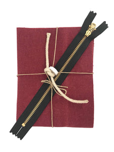 A small piece of folded red waxed canvas, a brass zipper, hemp rope, and role of leather tape, tied in a bow with twine.