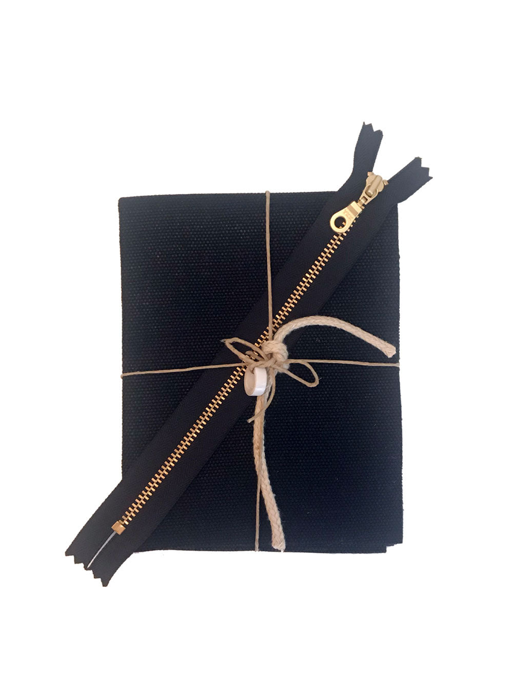 A small piece of folded black waxed canvas, a brass zipper, hemp rope, and role of leather tape, tied in a bow with twine.