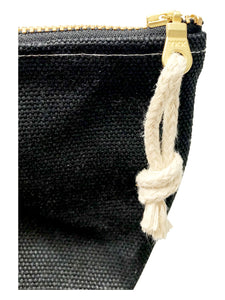 A close up of a black waxed canvas pouch with hemp zipper pull tied through the zipper pull.