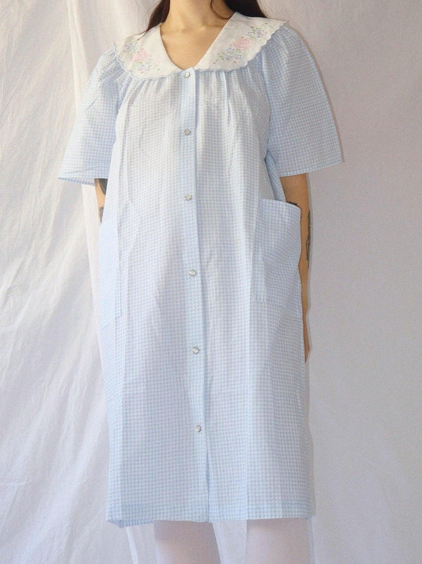 Vintage pastel blue housecoat dress in seer sucker fabric. Embroidered collar details, one of a kind. Dead stock, mint condition. 100% cotton. Size small, fits over sized. The Wilde Shop