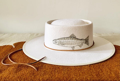 Ivory colored hat with silver toned fish hand embroidery and leather hatband and chin strap, resting on rust colored vintage textile