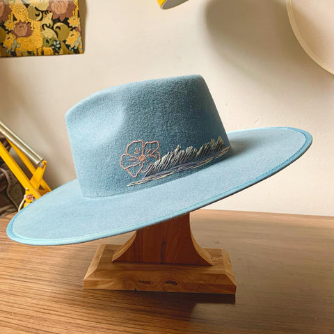 Light blue hat with abstract blue landscape and coral poppy hand embroidered on it, resting on wooden hat stand.