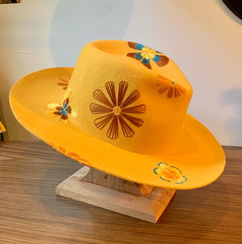 Mustard colored hat with retro flowers hand embroidered on it, resting on wooden hat stand.