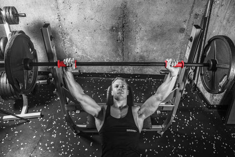 Mike Wood, qualified personal trainer and sport scientist, using a pair of red Symagrips® fitted on barbell gym equipment to provide him with stability, correct posture, proper form, and safety whilst working out.