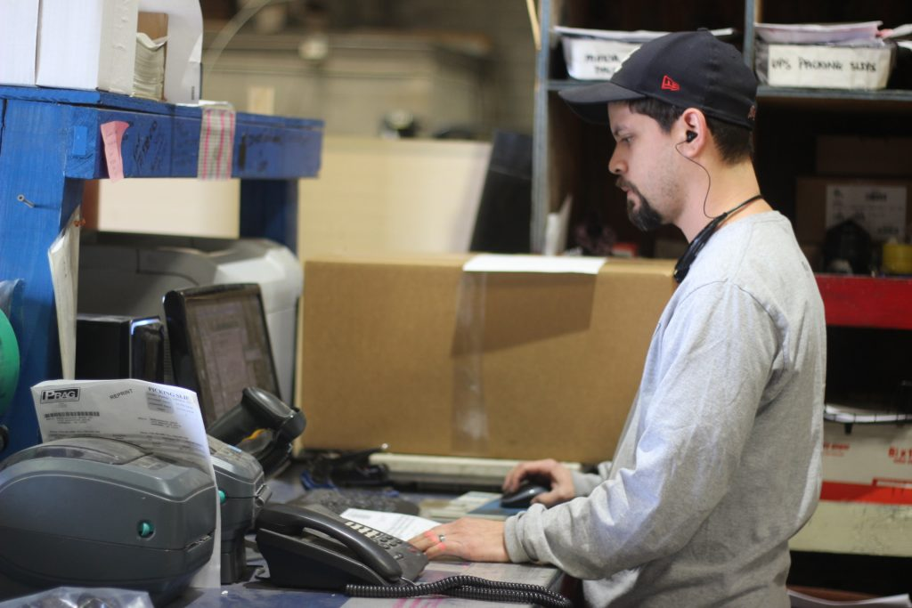 Employee working on shipping orders at Gasket Supply