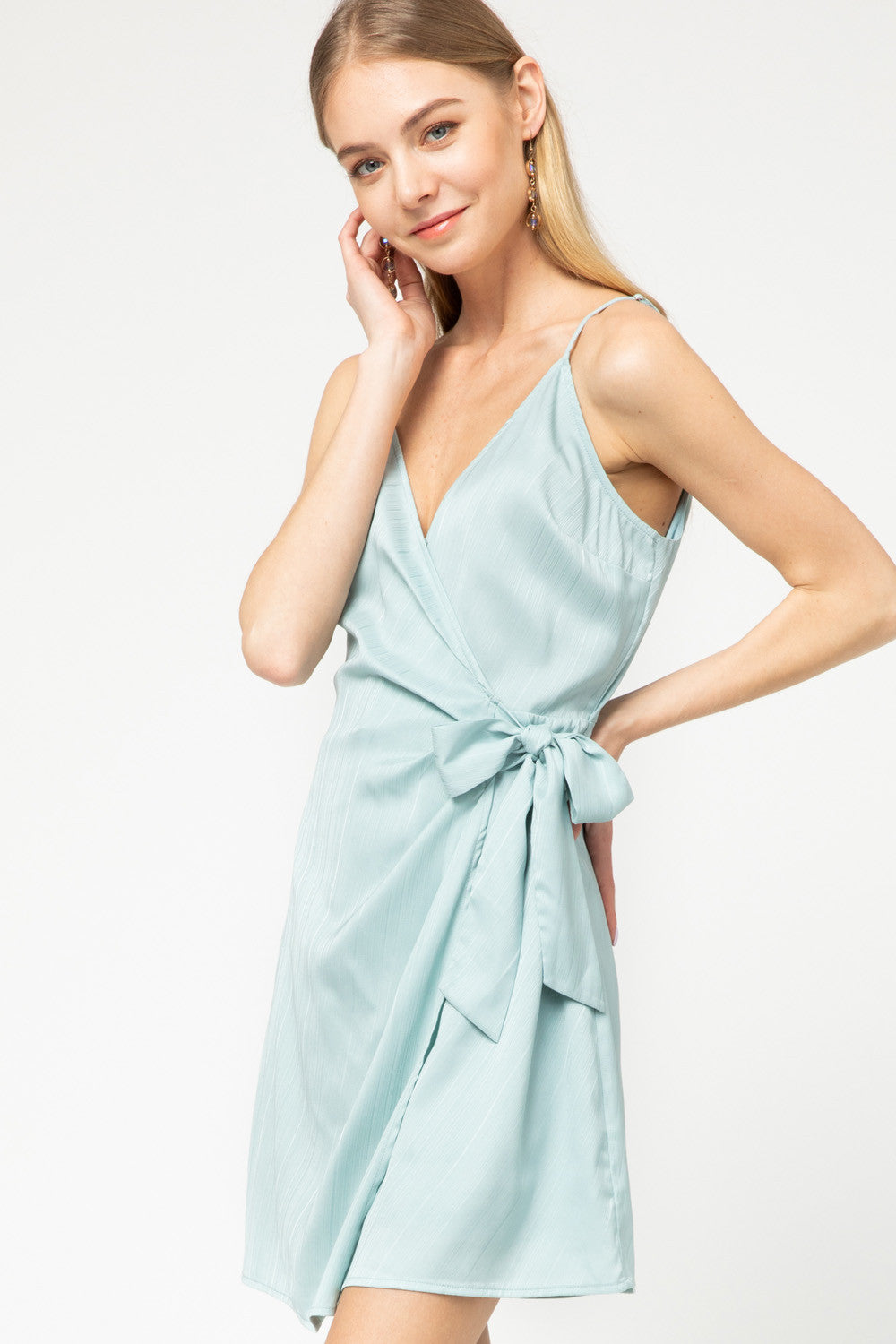 Textured satin sleeveless surplice wrap dress featuring self-tie detail at waist. Adjustable straps. Lined. Semi-sheer