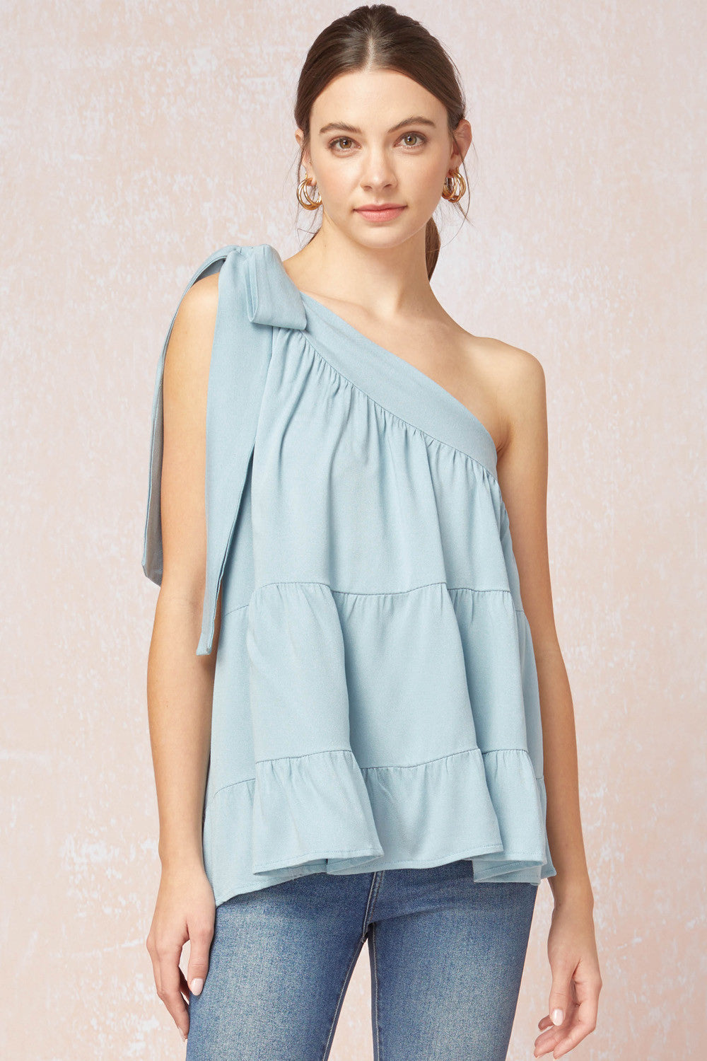 Solid tiered one-shoulder top featuring self-tie detail at shoulder