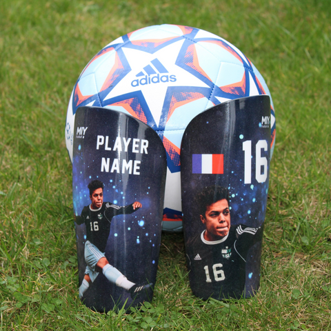 Pair of personalised football shin guards against a football