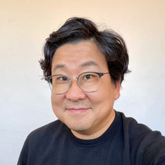 Nick Cho wearing a black sweater, smiling at you with a light beige background